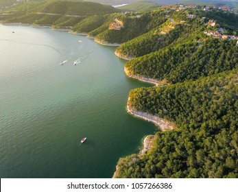 Aerial trees and cliff rock wall, bluffs at Lake Travis, Austin, Texas, USA. Luxury vacation homes and house on coastline. Looking down houses in community, ocean crystal background