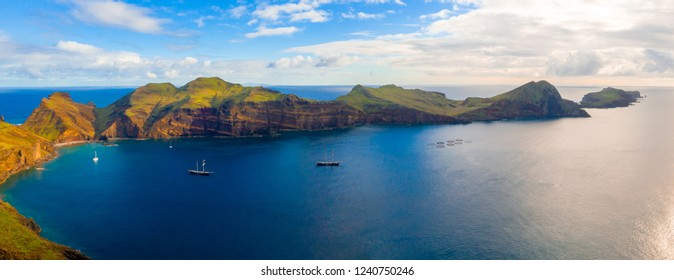Aerial tropical island view in the middle of the ocean with rocky cliffs and green fields