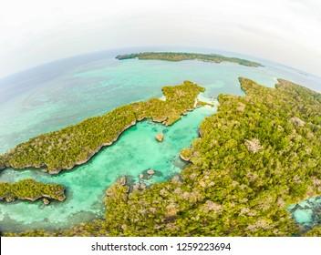 Aerial: tropical paradise pristine coast line rainforest blue lake at Bair Island. Indonesia Moluccas archipelago, Kei Islands, Banda Sea. Top travel destination, best diving snorkeling.