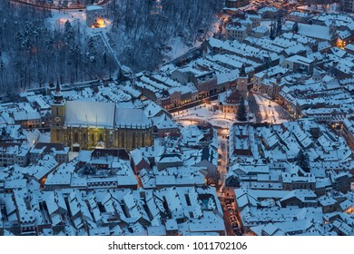 Aerial twilight view of the snowy Council Square in the historic center of Brasov city, Romania.
