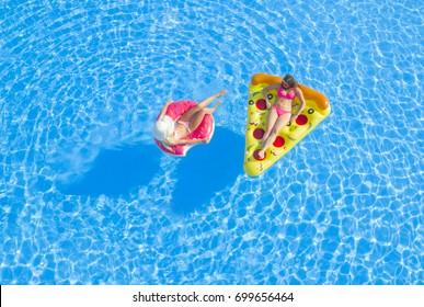 AERIAL: Two cheerful girlfriends lying on inflatable floaties, relaxing in pool