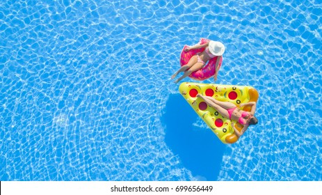 AERIAL Two cheerful young women enjoying on inflatable floaties chatting in pool