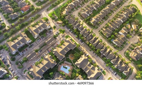 Aerial typical multi-level apartment building with swimming pool, surrounded by green garden and rows of cars in parking lots in Houston, Texas, US. Residential recreation concept. Warm light. Vintage