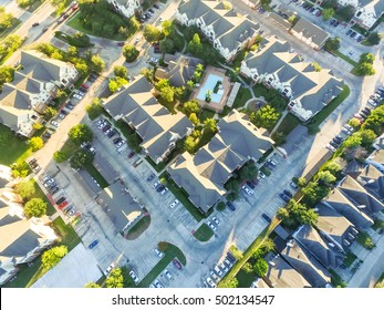 Aerial typical multi-level apartment building with swimming pool, playground, surrounded by green garden and rows of cars parking lots in Houston, Texas, US. Residential recreation concept. Warm light