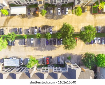 Aerial typical multi-level apartment complex building in USA.  Row of car in cover, uncovered, disabled handicap parking lots surrounded by green trees. Urban housing, rental market, landlord-tenant