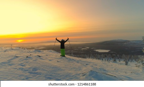 AERIAL: Unrecognizable female skier looks over the spectacular Lapland at sunset. Young woman celebrates reaching the summit on her skis on a sunny winter evening. Picturesque wintry nature in Finland