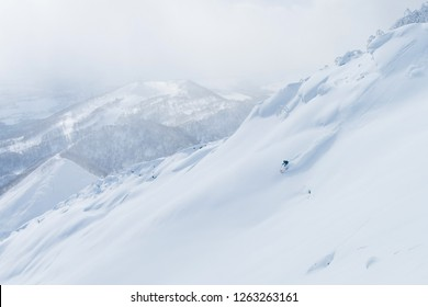 AERIAL: Unrecognizable man shredding the snowy mountain terrain while on fun ski trip in Japan. Flying above extreme skier riding off trail and through the fresh powder snow in picturesque Niseko.