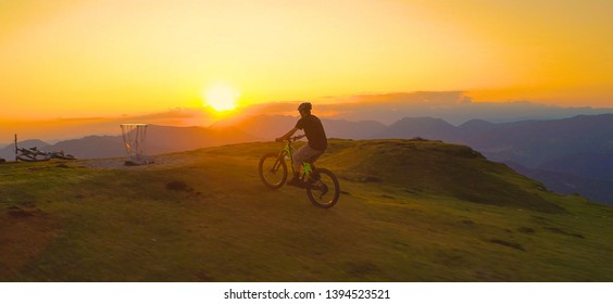 AERIAL: Unrecognizable mountain biker riding his bicycle up a grassy hill at picturesque sunset. Young male tourist enjoying a scenic mountain bike ride on an ebike on a beautiful summer morning.