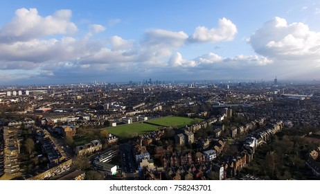 Aerial Urban Downtown View of London City with Green Pitch and Blue Sky Clouds. Landmarks in the Background at Distance