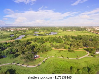 Aerial urban green park with suburban Houston neighborhood in distance. S-curved pathway, tree, grassy lawn, trail for jogging, running, exercising outdoor, large Tai Chi circle of Ying Yang in middle