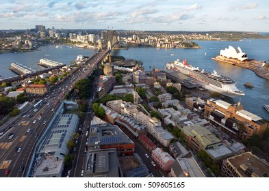 Aerial urban landscape view of Sydney Harbor at sunset in New South Wales, Australia.