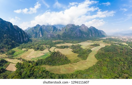 Aerial: Vang Vieng backpacker travel destination in Laos, Asia. Dramatic sky over scenic cliffs and rock pinnacles, rice paddies valley, stunning landscape.