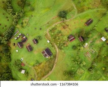 aerial veiw of rural road, green field, trees and buildings. drone shot
