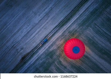 Aerial, vertical view of the night landing red-blue hot air balloon against diagonal pattern of dry field. Shining red hot air balloon illuminating surroundings against dark ground with pick-up car.