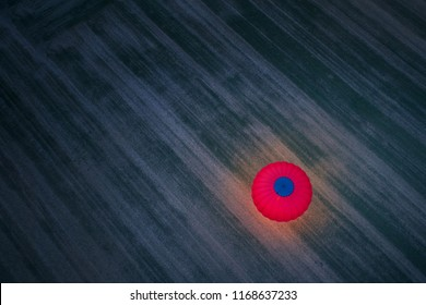 Aerial, vertical view of the night landing red-blue hot air balloon against diagonal pattern of dry field. Shining red hot air balloon illuminating surroundings against dark ground. Artistic view.