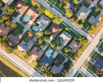 Aerial vertical view residential houses with swimming pool in Carrollton, Texas, USA during fall sunset. Top view row of single-family homes with garden, driveway and attached garage