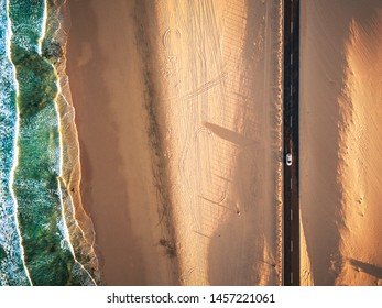 Aerial vertical view of yellow tropical sandy beach with black long way road and car traveling - ocean blue waves and shore - sunset time with long beautiful shadow - concept of summer vacation