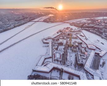 Aerial video winter panorama Peter and Paul Fortress, frozen Neva river at sunset, Smoke from pipes, Petrovskaya embankment, Winter Palace, Palace bridge