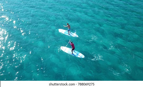 Aerial view of 2 men exercising sup board in turquoise tropical clear waters