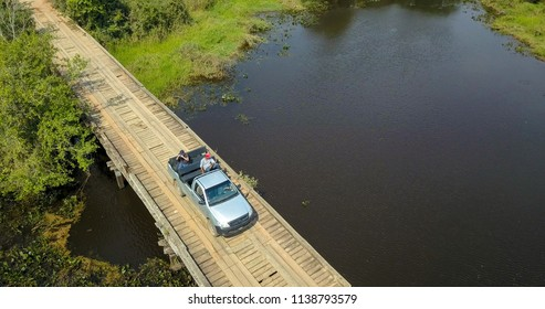 """Aerial view of 4x4 vehicle on the """"Transpantaneira"""" road with river and forest in the background in the Pantanal wetlands on sunny day."""