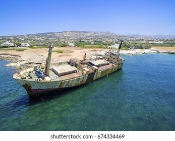 Aerial view of abandoned ship wreck EDRO III in Pegeia, Paphos, Cyprus. The rusty shipwreck is stranded on Peyia rocks at kantarkastoi sea caves, Coral Bay, Pafos, standing at an angle near the shore.