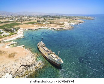 Aerial view of the abandoned ship wreck in Pegeia, Paphos, Cyprus. The rusty shipwreck is stranded on Peyia rocks at the kantarkastoi sea caves near Coral Bay in Pafos, standing at an angle on coast.