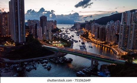Aerial view of the Aberdeen Harbour  (Aberdeen Typhoon Shelter), Ap Lei Chau Bridge, and the buildings on two sides of the harbour during sunset.