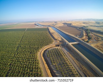 Aerial view above California aqueduct running through almond plantations and cultivated fields, drone shoot of farmland landscape