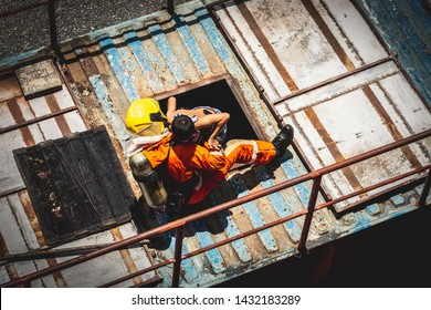 Aerial View Above of Child being carried by his fireman to help child on the burning warehouse roof, Fire escape emergency staircase above. Fire and Firefighter training school.