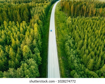 Aerial view from above of country road through the green summer forest in summer Finland. drone photography