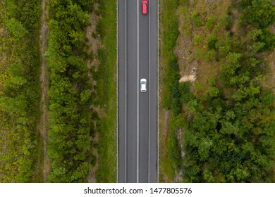 Aerial view from above of a country road through a green forest, drone shooting