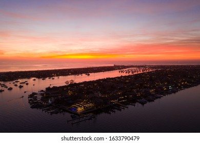 Aerial view from above Newport Beach harbor vacation destination after sunset during orange sky twilight with boats in the water below and the horizon in view