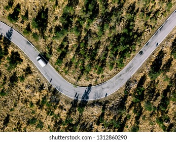 Aerial view from above of a rural landscape with a curvy road and white car in Italy. Drone photography