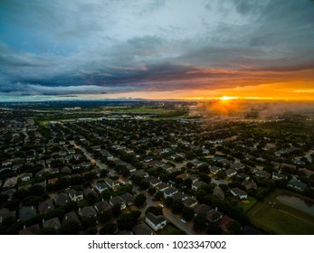 Aerial view above suburb neighborhood real estate market new home ownership and city living in Suburbia community north of Austin , Texas During amazing sunset with spots of ominous fog on the horizon
