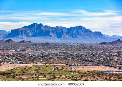 With an aerial view above swimming pools and golf courses loom the Superstition Mountains in Apache Junction, Arizona