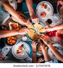Aerial view from above for table and hands and a lot of food and drinks. celebration and party event concept image. all hands taking from the same plate to share and enjoy the friendship.  eating