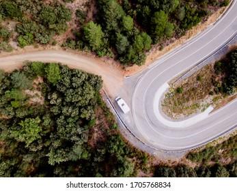 Vista aérea de una casa de motos de aventura en un camino de montaña a través de un bosque