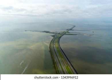 Aerial view of the Afsluitdijk at Kornwerderzand, Friesland. The dike separates lake IJsselmeer from sea Waddenzee. The highway is motorway A7 and the sluices are lock LORENTZSLUIZEN. Cloudy sky.