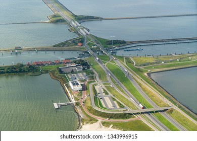 Aerial view of the Afsluitdijk at Kornwerderzand, Friesland. The dike separates lake IJsselmeer from sea Waddenzee. The highway is motorway A7 and the sluices are lock LORENTZSLUIZEN.