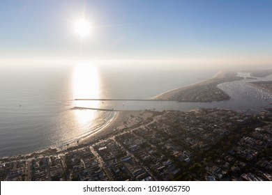 Aerial view of afternoon sun and coastal fog over the entrance to Balboa Bay and Newport Beach Harbor in Orange County, California.