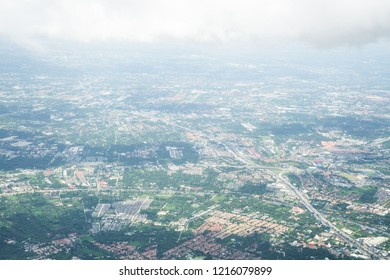 Aerial view from airplane window.  Highway road, urban town, tree and hometown village roof landscape. Big white clouds and shadow in sunny day. North of Bangkok, Thailand. Travel concept.