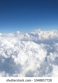 aerial view from airplane window of sky above clouds