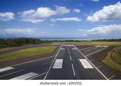 Aerial view of airport runway on coastline of Maui, Hawaii.