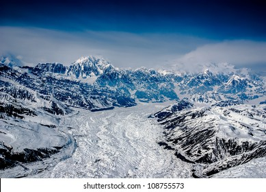 Aerial View of Alaskan Glacier Leading up to Mt. McKinley, Spewing Out Snow and Clouds.  The Great Alaskan Wilderness, Denali National Park, Alaska.  A Beautiful Snowscape of Rock, Snow, and Ice.