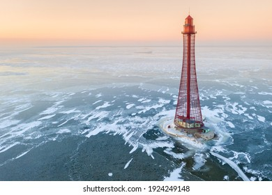 aerial view to alone red lighthouse in frozen sea under pink sky in winter sunset with copy space