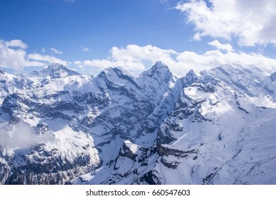 Aerial view of the Alps mountains in Switzerland. View from helicopter in Swiss Alps. Mountain tops in snow. Breathtaking