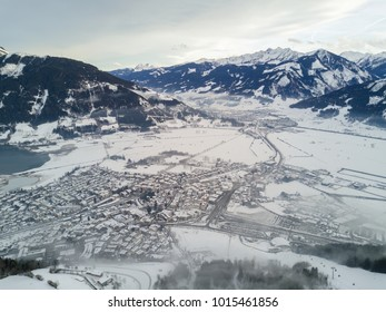 Aerial view of the Alps. The resort village of Zell am See near the lake. Peaks of mountains in the snow in winter. Ski resort in Austria. Leisure. Winter sports