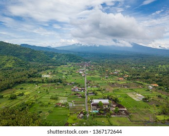 Aerial view of Amed in Bali, Indonesia. Mount Agung volcano in the background, partially covered by clouds.