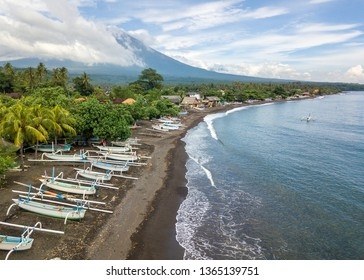 Aerial view of Amed beach in Bali, Indonesia. Traditional fishing boats called jukung on the black sand beach and Mount Agung volcano in the background, partially covered by clouds.