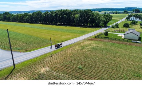 Aerial View of Amish Farm Land and a Horse and Buggy Going Down the Road